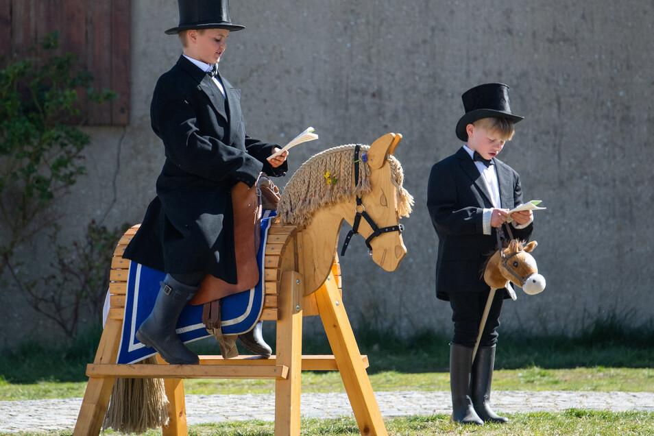 Zwei Jungs spielen auf ihrem Hof in Rosenthal mit einem Holzpferd Osterreiten. Die eigentlichen Prozessionen müssen wegen der Corona-Pandemie ausfallen.