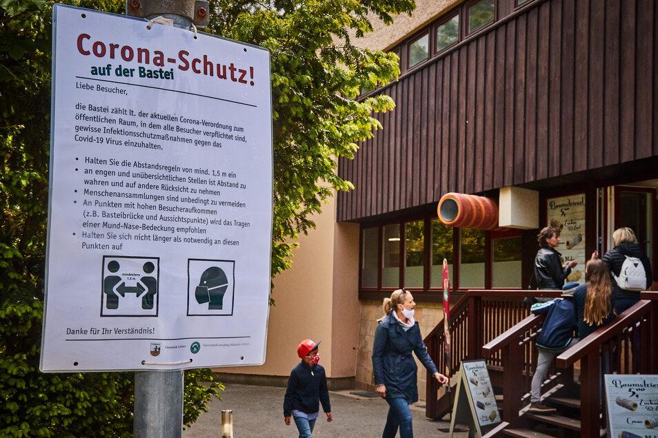 Die Corona-Schutz-Regeln gelten auch an der Bastei und auf den Wanderwegen. Eine Frau und ein Kind laufen mit Mund- Nasenschutz.