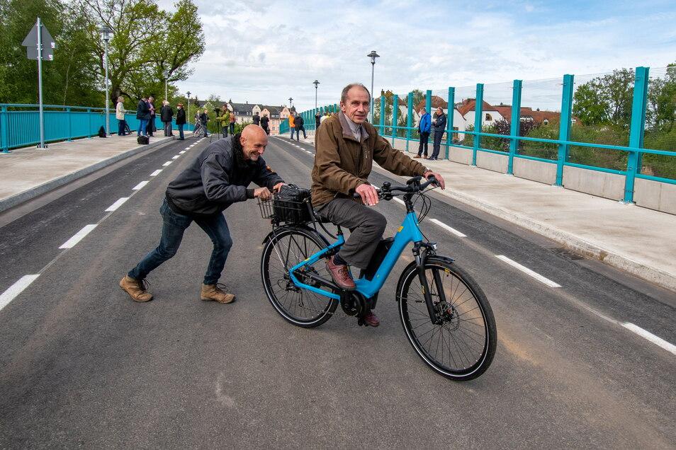 Lothar Seifert fährt mit seinem Rad als erster über die Brücke. Sven Weißflog, Chef der Firma Bau Logistik, schiebt ihn an.