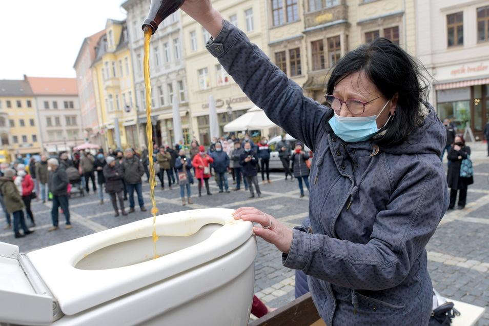 """Protestaktion auf dem Zittauer Markt gegen den Corona-Lockdown. Elke Mäffert vom """"Irish Pub"""" schüttet abgelaufene Getränke ins Klo."""