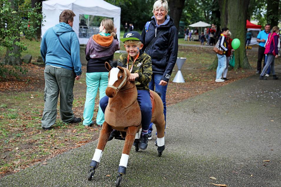"""Der siebenjährige Tim reitet ein mechanisches Pferd. """"Das ist gar nicht so einfach wie es aussieht."""""""