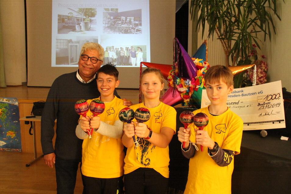 Tyron, Timea und Lucian (v.l.) vom Schulchor freuen sich über die Rasseln, die Dr. Zamora als Dank für den 1.000-Euro-Scheck an die Sorbische Grundschule übergab.