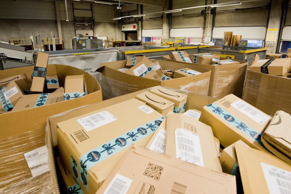 Pakete des Versandhändlers Amazon liegen in einem Paketzentrum von Deutsche Post und DHL.