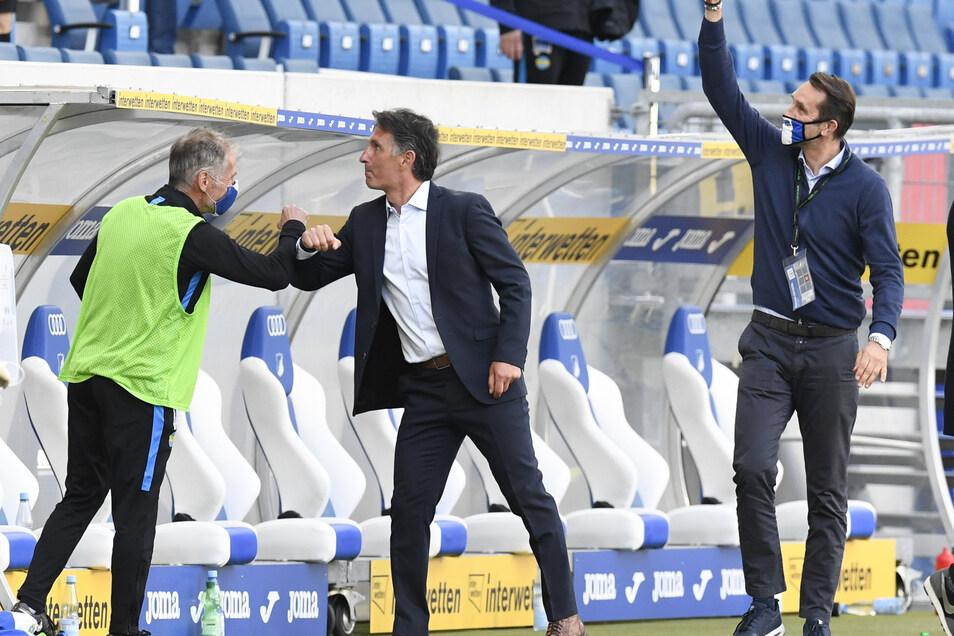 Bruno Labadia (M), Trainer von Hertha, und Michael Preetz (r), Manager des Vereins, freuen sich am Spielfeldrand über den 0:3 Sieg ihrer Mannschaft.