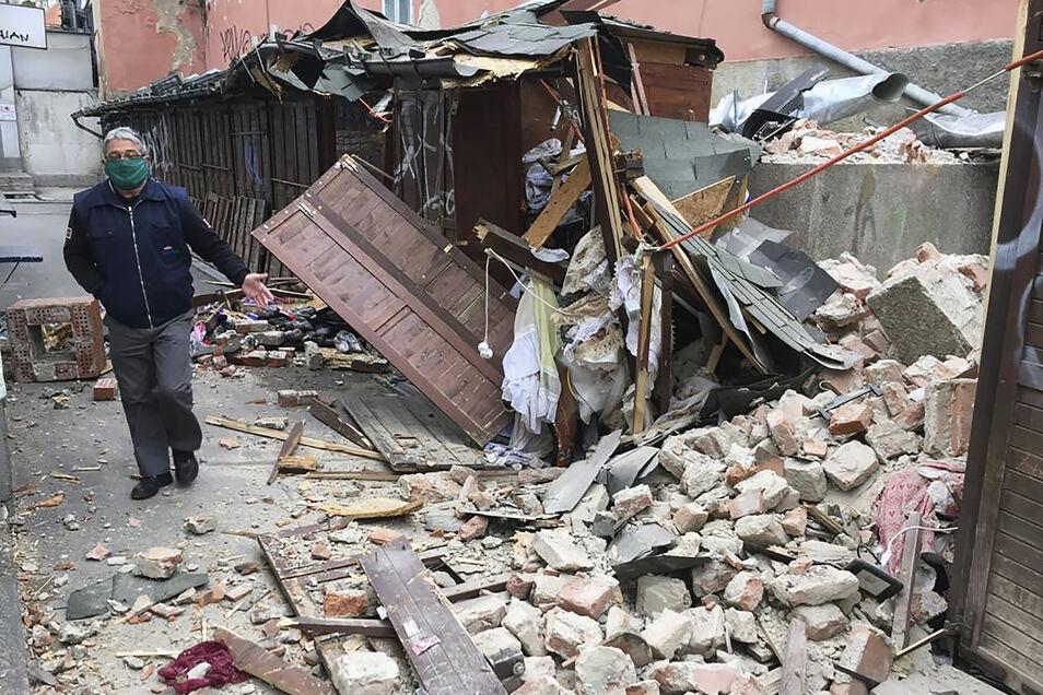 Ein Mann mit Mundschutz inspiziert die Schäden, die durch die Erdbeben verursacht wurden.
