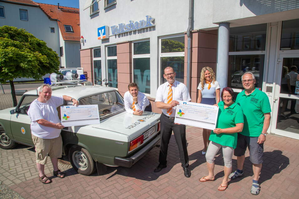 Bereichsleiter Michael Wünsche übergibt die Schecks an Blaulichttreff-Organisator Andreas Pallesche (links) sowie an die Verkehrswächter Stephan Lachnitt und Ruth Stangret (rechts).