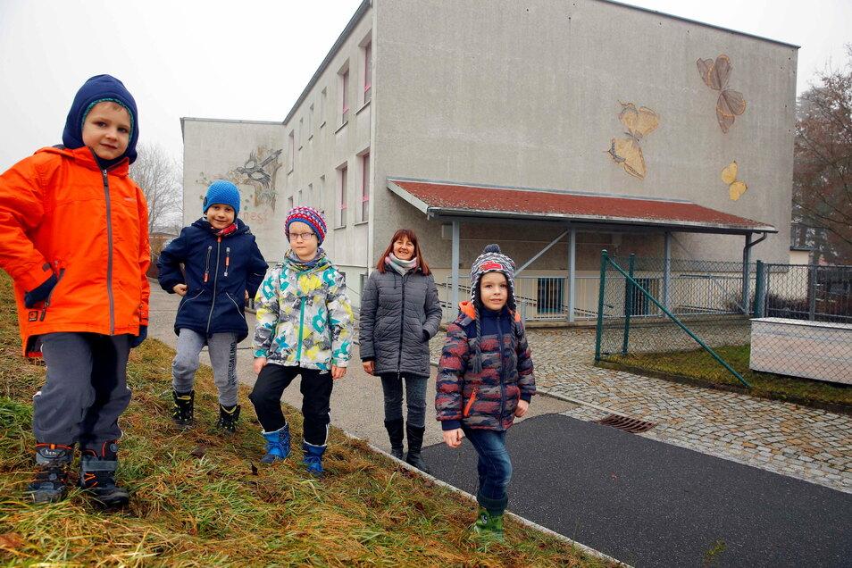 Die Vorschüler Luke, Jonas, Nils und Joel (v.l.) sowie Erzieherin Antje Kühne freut es: Die Außenfassade ihrer Kita Grüner Weg in Elstra soll in diesem Jahr saniert werden.