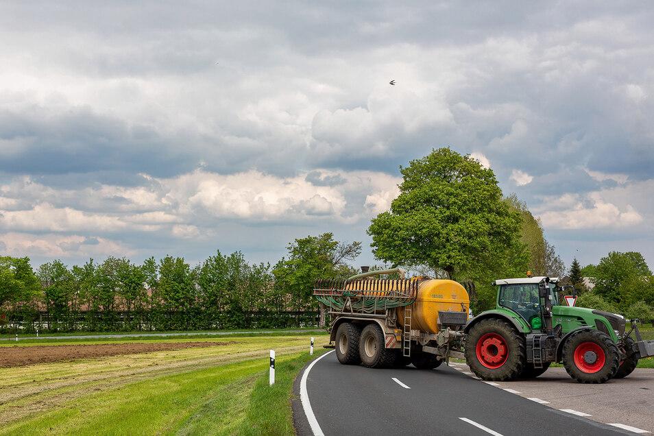 Ein landwirtschaftliches Gespann ist oberhalb von Sadisdorf unterwegs. Die Jungviehanlage im Hintergrund ist wegen ihrer Geruchsbelästigung in die Diskussion geraten.