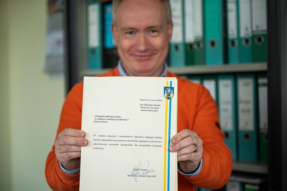Sebastian Beutler, Redaktionsleiter der Saechsischen Zeitung Görlitz mit der Urkunde des Bürgermeisters von Zgorzelec, Rafal Gronicz.