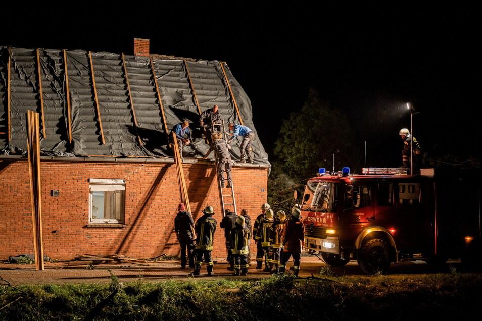 Niedersachsen, Berumerfehn: Feuerwehrleute und Helfer reparieren das Dach eines beschädigten Hauses.