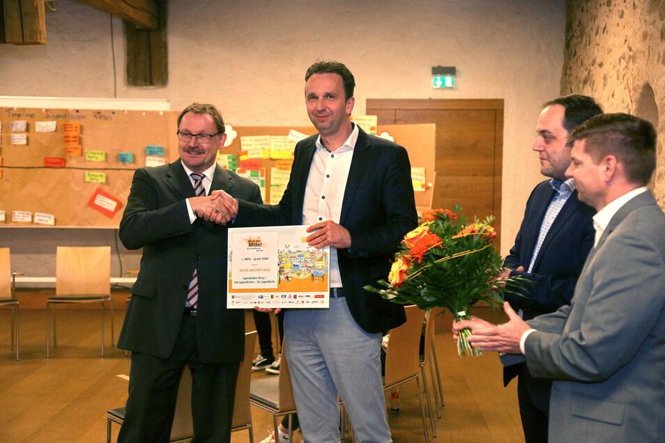 """Riesas Oberbürgermeister Marco Müller (CDU, 2.v.l.) nahm stellvertretend den Gewinn aus dem Wettbewerb """"Ab in die Mitte"""" von IHK-Geschäftsführer Thomas Ott entgegen."""
