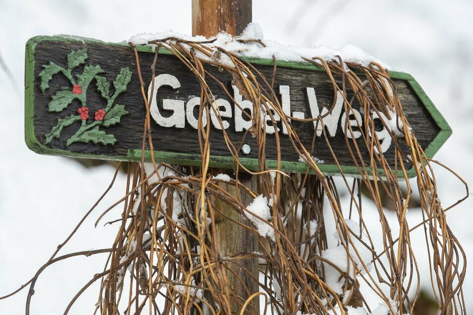 Der Goebel-Weg führt im Forstgarten zu einem stattlichen Spalier aus Stechpalmen, wie die Schnitzerei auf dem Wegweiser anzeigt.