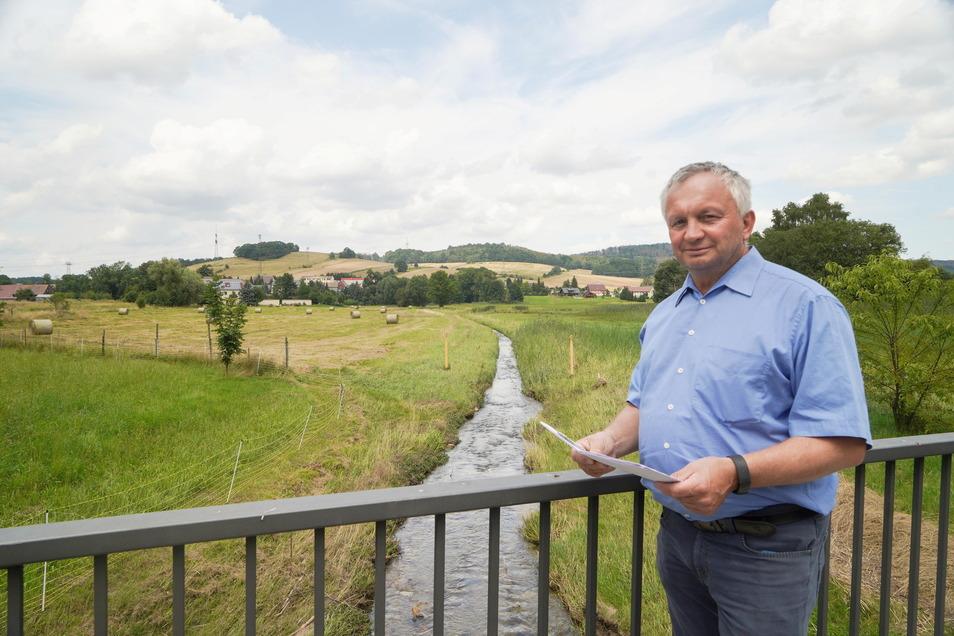 In der Wesenitzaue hinter Andreas Hultsch, etwa an der Baumgrenze in der Mitte des Bildes, soll der Damm entstehen, der Wasser aufhält und Anwohner schützt.