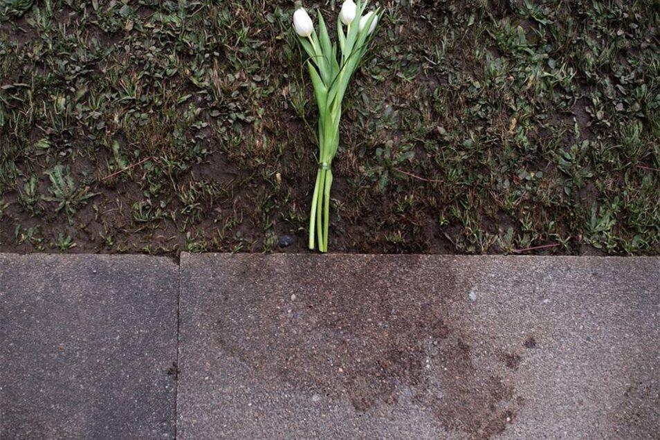 Weiße Tulpen liegen neben einer getrockneten Blutlache an der Stelle, an der der Tote aufgefunden wurde.