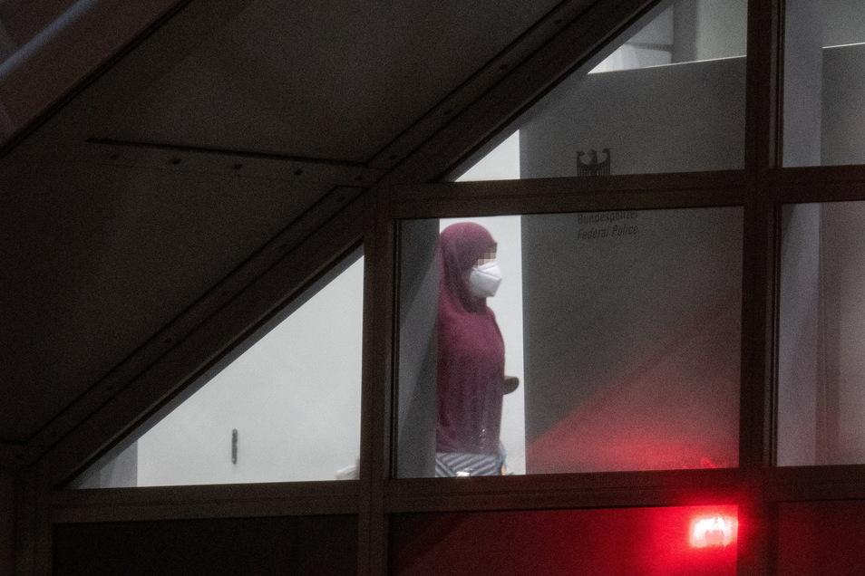 Eine verschleierte Frau mit einer Maske betritt aus der Gangway einer Chartermaschine heraus einen abgeschirmten Bereich der Bundespolizei am Flughafen Frankfurt.