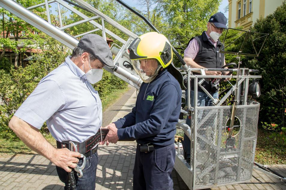 Für die Sicherheit der beiden Musiker sorgt Feuerwehrmann Jens Trenkler. Gurttragen ist Pflicht im Korb der Drehleiter.