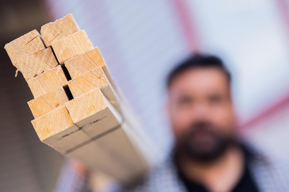 Ein Dachdecker trägt ein Bündel mit Dachlatten. Der Baustoff Holz ist derzeit sehr knapp.