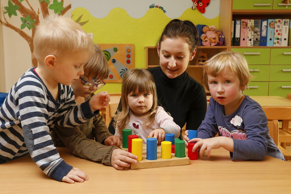"""Enno, Helena, Tamara und Roberta (von links) spielen mit der neuen Kollegin Ilona Schega (Zweite von rechts) in Schönau-Berzdorfs Kita """"Hutbergzwerge""""."""