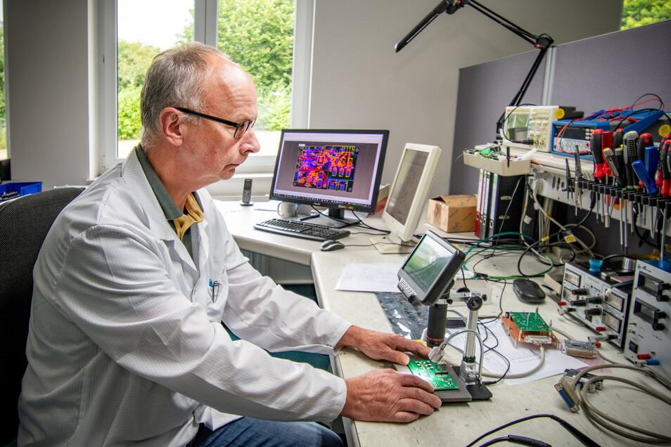 Detlef Wagner prüft eine Leiterplatte und schaut sich diese unter einem speziellen Mikroskop an.