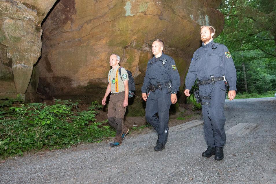 Nationalparkwächter Steffen Elsner (links) mit zwei Polizisten auf dem Weg zu den Schrammsteinen. Sechs Teams gingen auf Streife, der Helikopter lotste sie aus der Luft.