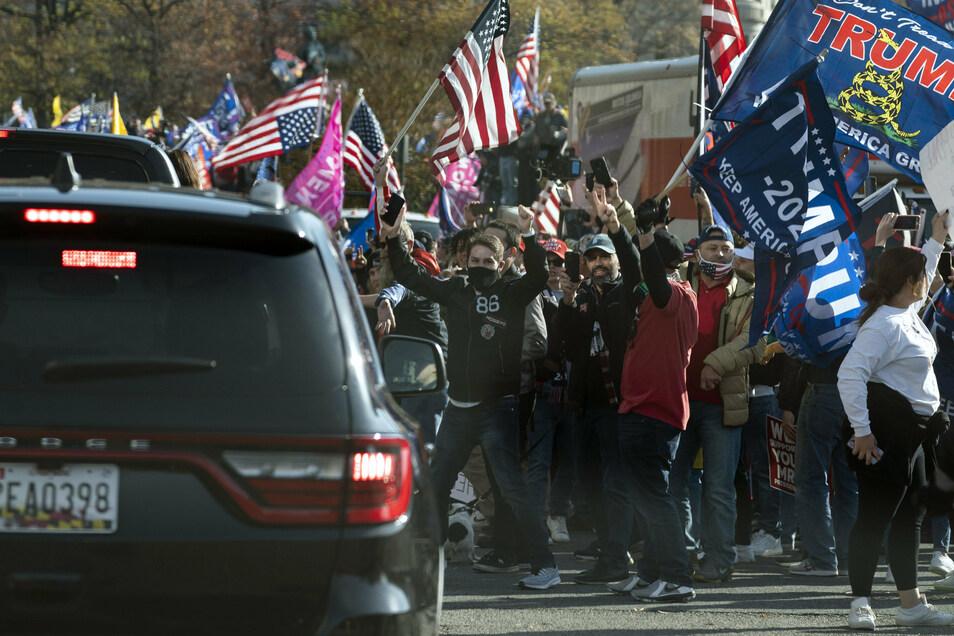 Der US-Präsident Trump fährt in einer Autokolonne an einer Gruppe von Anhängern vorbei, die zu dessen Unterstützung in der Nähe des Weißen Hauses demonstrieren.