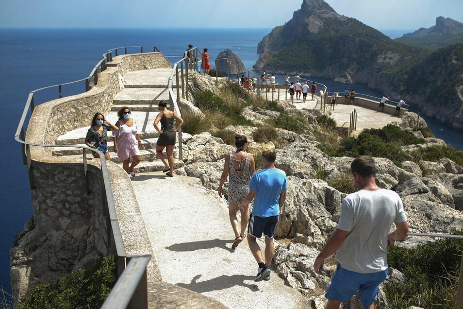 Touristen gehen zu einem Aussichtspunkt in Pollenca auf Mallorca. Auch hier gilt die Maskenpflicht.