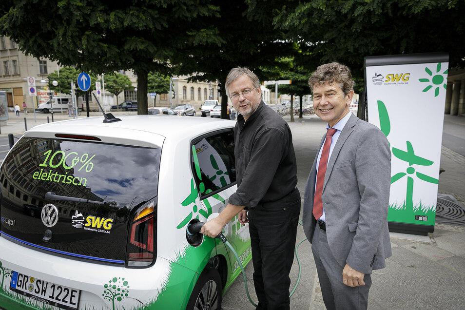 Bürgermeister Michael Wieler und Stadtwerke-Chef Matthias Block testen am Dienstag die neue Ladesäule am Bahnhof.