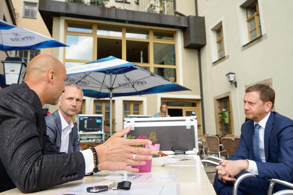 Sachsens Ministerpräsident Michael Kretschmer (rechts) hat Sandro Reichel (Mitte) vom Best Western und André Domsch vom Alten Bierhof in Bautzen besucht. Ganz Sachsen konnte dabei sein - per Facebook-Livestream.