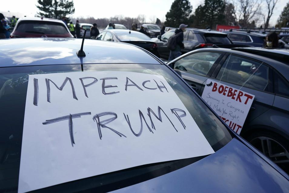 Auf der Heckscheibe eines Autos liegt ein Plakat, auf dem die Amtsenthebung von Präsident Donald Trump gefordert wird. Autofahrer fordern während eines Protests in Denver das Impeachment.