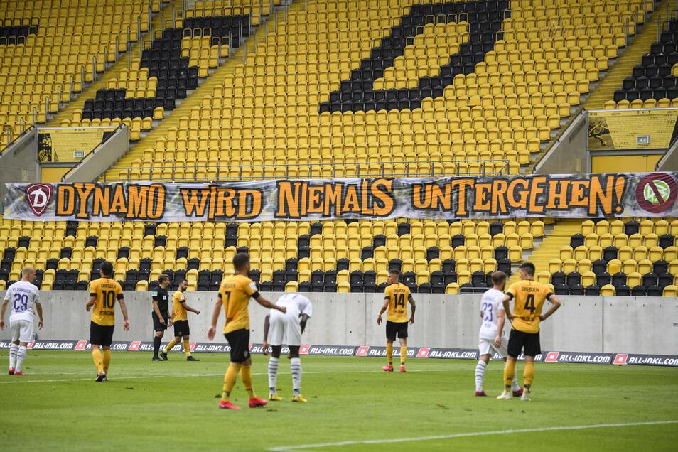 """Ein Banner mit der Aufschrift """"Dynamo wird niemals untergehen!"""" hängt auf der Tribüne."""