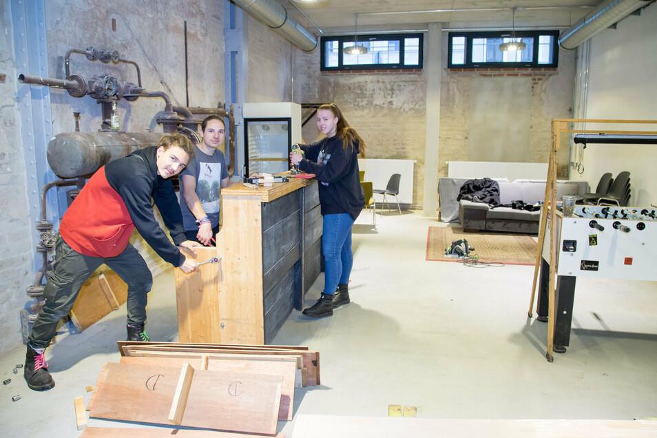 Luboš Suchy, Sören Vogel und Charlotte Henkel (v.l.) bauen eine Bar in den Jugendtreff ein. Der Raum bewahrt Industriecharme.