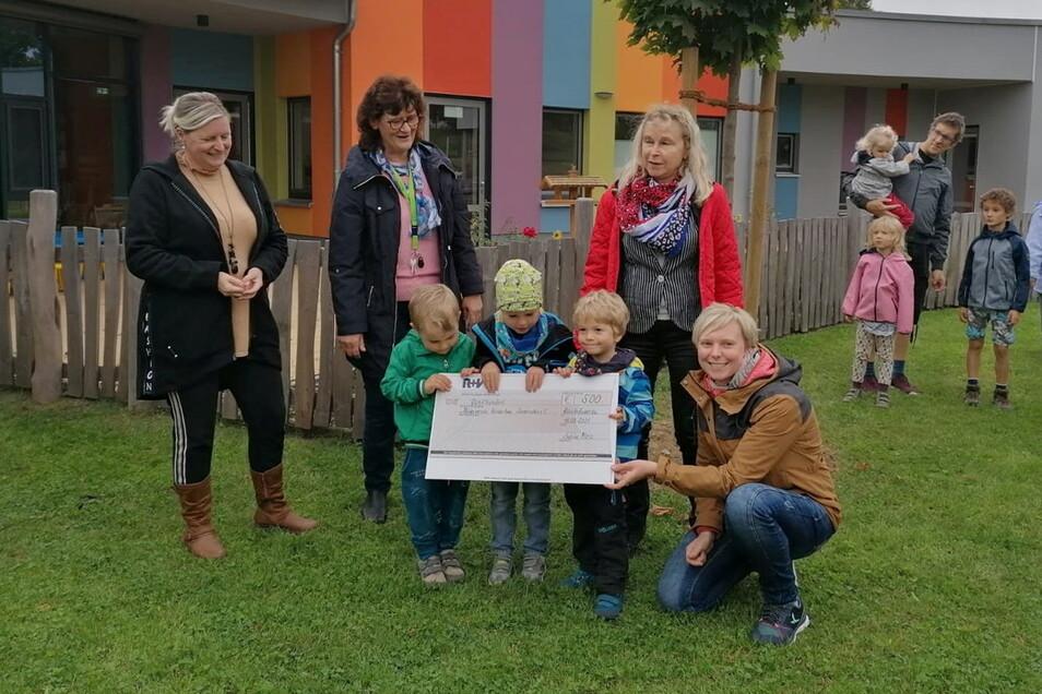 Sabine Merz (2.v.r.) von der Bautzener R+V-Generalagentur überreicht den Kinder vom Kinderhaus Sonnenschein in Bischofswerda einen symbolischen Scheck.