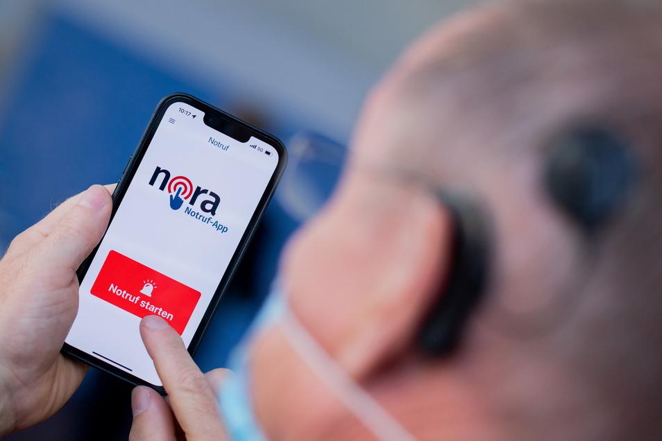 Ein hörgeschädigter Mann testet die neue Notruf-App Nora auf dem Display seines Mobiltelefones.
