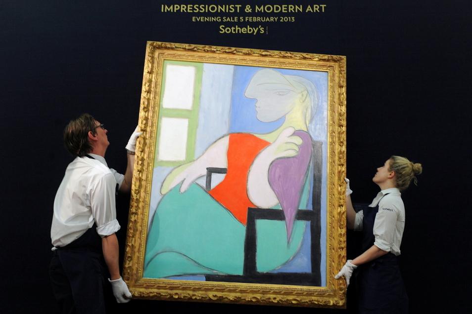 """Mitglieder des Auktionshauses Sotheby's hängen das Gemälde """"Sitzende Frau am Fenster"""" von Pablo Picasso in London auf."""