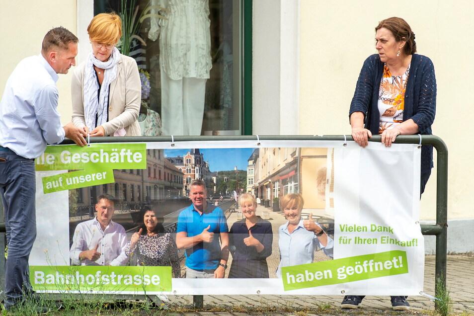 DDV-Elbland-Geschäftsführerin Petra Gürtler (r.) befestigt mit den beiden Händlern, Susan Gommlich und Uwe Marx, ein Transparent am Geländer vor der Lößnitzperle.