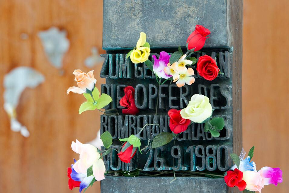 Blumen stecken an einem Denkmal, das an die Opfer des Attentats auf das Oktoberfest erinnert.