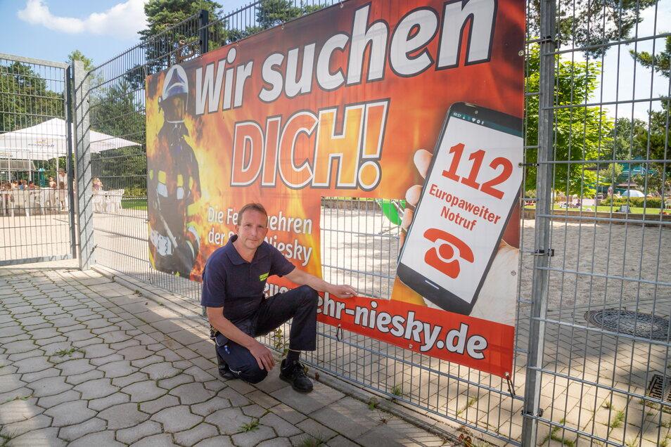 Das Plakat, mit dem die Nieskyer Feuerwehr am Zaun des Waldbades um Mitglieder wirbt, wurde jetzt mutwillig beschädigt. Vereinsvorsitzender Jens Trenkler hat den Fall bei der Polizei angezeigt.