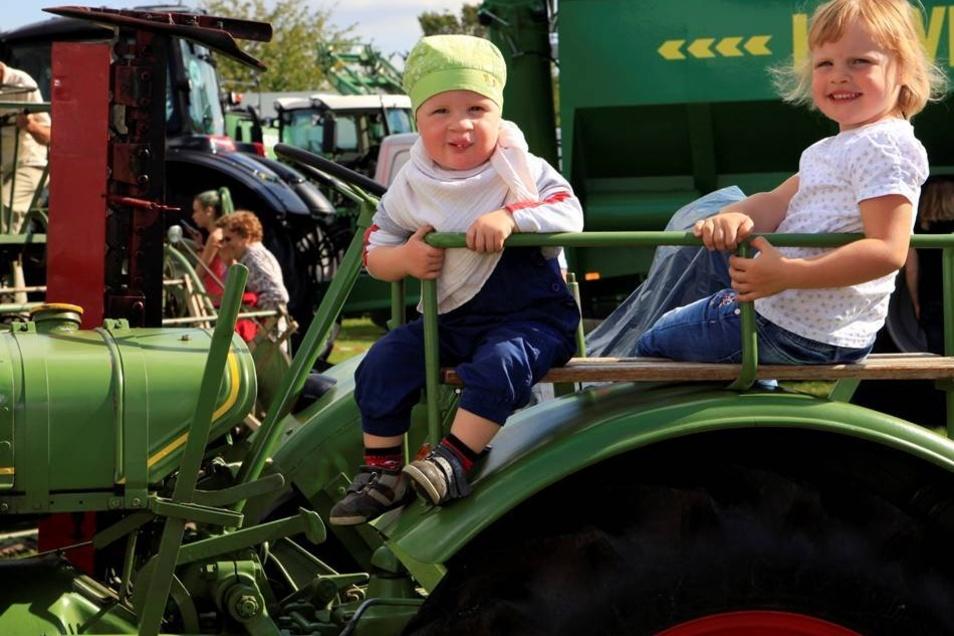 Messe und Veranstaltungspark: Louis, 2 Jahre, und Vivien, 4 Jahre, macht es Spaß auf dem historichen Traktor.