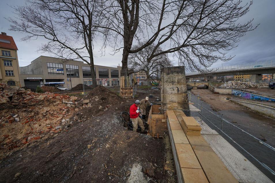 Mitarbeiter der Firma Kühnapfel Spezialbau bereiten Betonarbeiten an der Weißeritzmauer vor. Bevor der Park umgestaltet wird, muss die Mauer saniert werden.