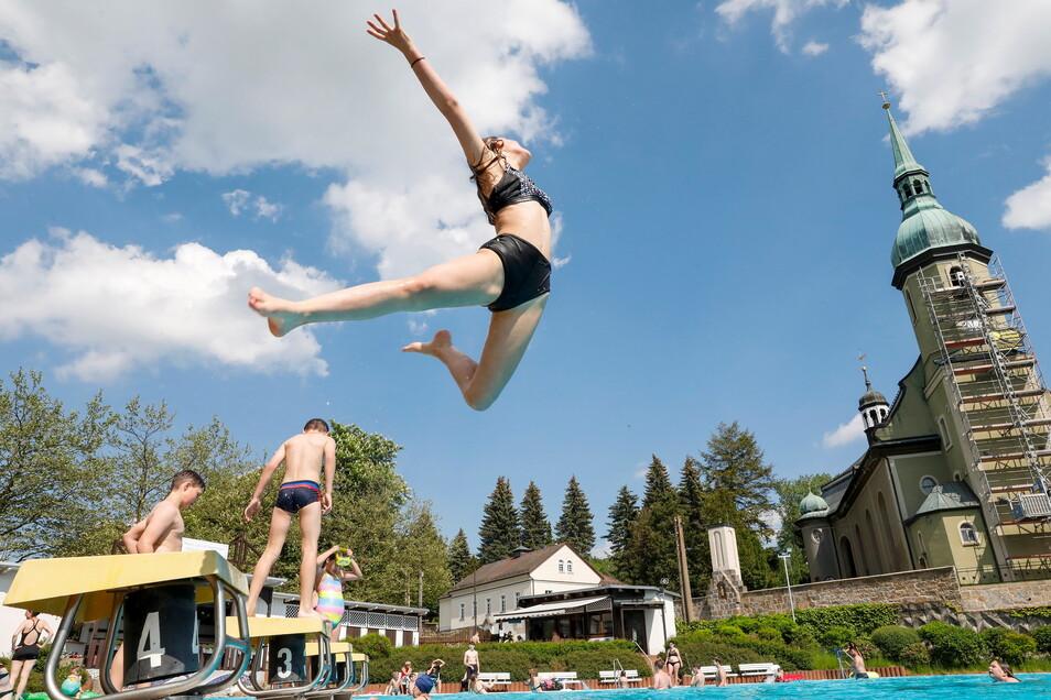 Dieses Mädchen springt ins Becken des Ebersbacher Freibades. Wie die anderen Badbesucher freut sie sich, dass am Sonnabend die Badsaison begonnen hat.
