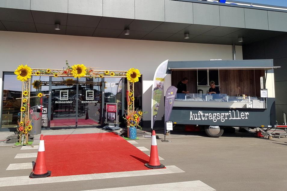 Mit einem roten Teppich und knallgelben Sonnenblumen begrüßte der neue Supermarkt seine ersten Gäste. Wer hier mehr als zehn Euro ließ, bekam einen Burger kostenlos.