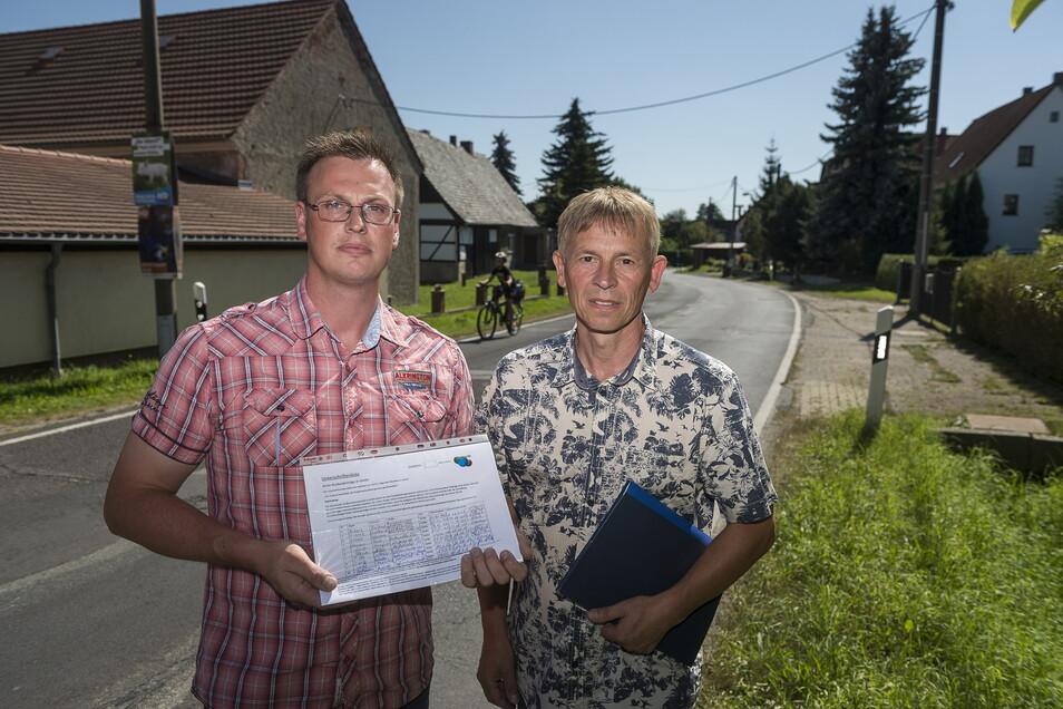 Tom Flach (l.) und Frank Lehmann stehen in Ludwigsdorf mit einer Unterschriftenliste zum Thema Straßenausbaubeitragssatzung.