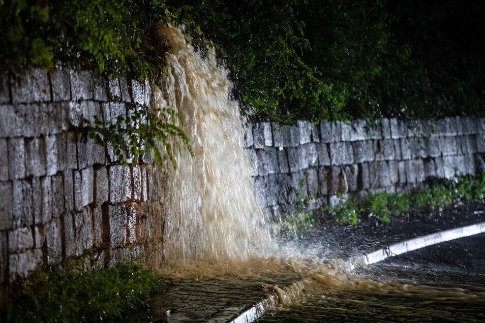Wassermassen dringen an der Weinsteige durch Büsche auf die Bundesstrasse B27.