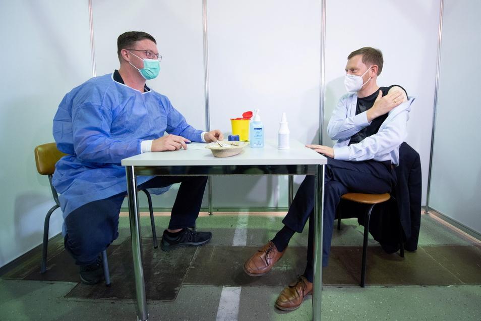 Michael Kretschmer (CDU, r) sitzt nach seiner Impfung mit dem Vakzin von Astrazeneca im Impfzentrum Sachsen neben dem Arzt Nikolas Ennker.