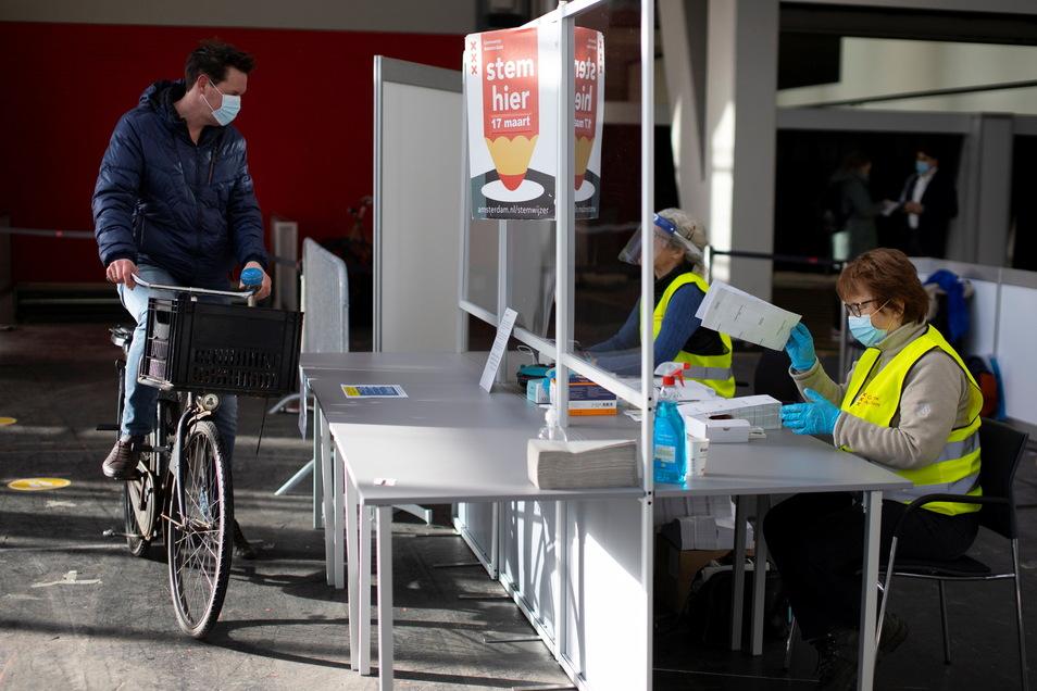 Ein Mann kommt mit seinem Fahrrad zur Stimmabgabe in ein Amsterdamer Wahllokal. Die Wahlen zum neuen niederländischen Parlament haben begonnen.