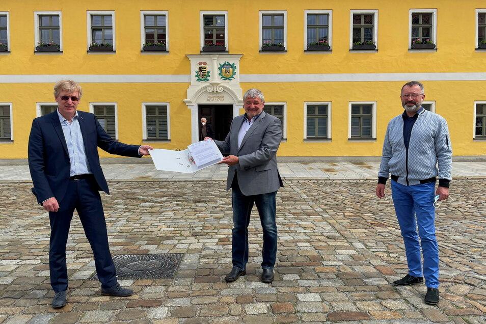 Bürgermeister Peter Mühle (Mitte) nimmt von Vertretern der Deutschen Telekom den Übergabebescheid entgegen.