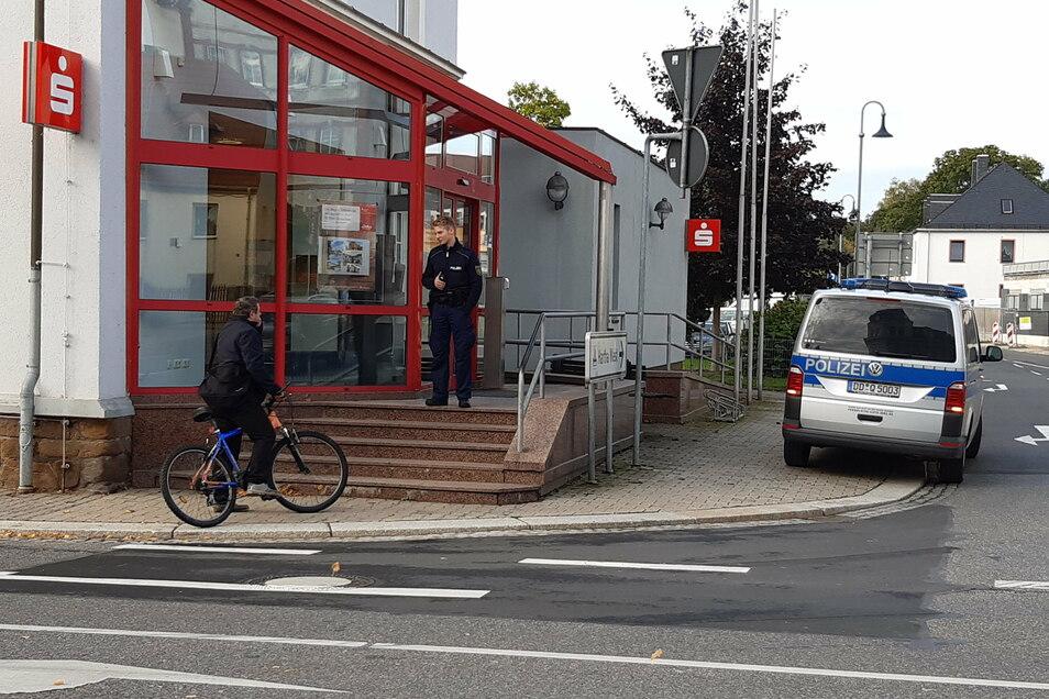 Ein Polizist steht nach dem Überfall vor dem Eingang zur Sparkasse in Hartha. Er weist eine Passantin darauf hin, dass die Filiale nicht betreten werden darf.