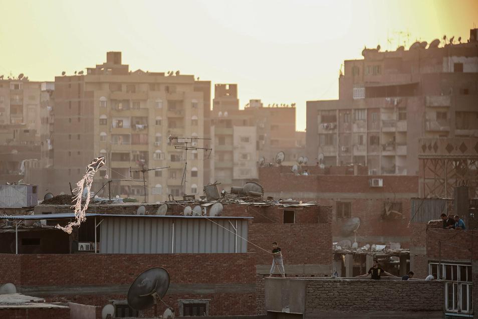 Ein Junge steht in Gizeh auf einem Dach und lässt einen handgefertigten Drachen über Wohnhäuser im Al-Munib-Viertel fliegen.