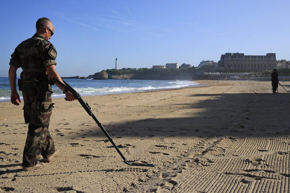 Ein französischer Soldat geht mit einem Minensuchgerät am Strand innerhalb der roten Zone mit dem Veranstaltungsort im Hintergrund entlang.