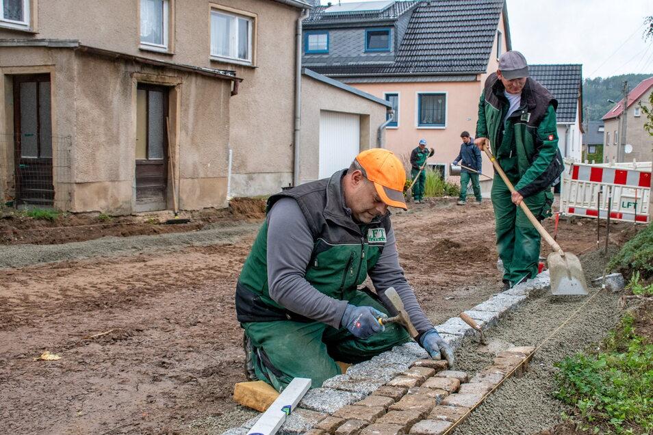 Mitarbeiter der Firma LFT arbeiten in Keuern gerade an den Straßen, nachdem die Leitungen im ersten Abschnitt verlegt wurden. Ein Teil der neuen Fußwege ist schon fertig.